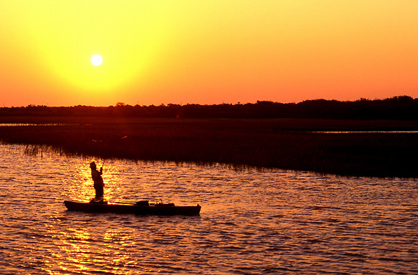 Stock photo of the silhouette of a man standing beside his kayak fishing at sunset