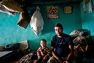 A father and his son inside the village home in Ropa Village, Himachal Pradesh, India