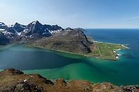 Overlooking colorful water of Flakstadpollen towards village of Flakstad, Flakstadøy, Lofoten Islands, Norway