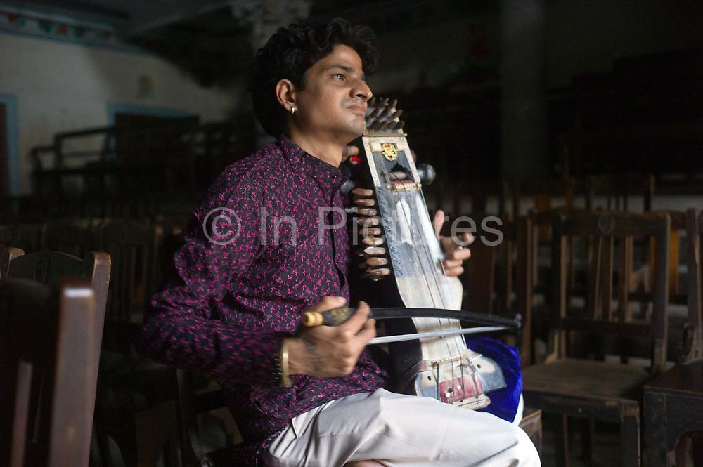Umesh Mishra, 26 a sarangi virtuoso tunes his instrument before a concert later that night at the Nrityagopal Smriti Mandir, a concert hall in Chandannagar, India