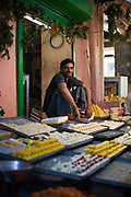 A man selling sweets on a stall in the backstreets of a Jaipur bazaar, Jaipur, India