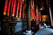 Woman praying behind the Golden Statue of Guanyin and Sudhana  from the Jade Buddha Temple interior in Shanghai. Asia, china.