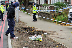 © Licensed to London News Pictures. 03/12/2013 London, UK. A teenager reads the tributes outside a house on the North Circular Road where a  17 year old boy has been stabbed to death. Officers were called to the address  in Palmers Green where they found the teenager from Haringey. Photo credit : Simon Jacobs/LNP