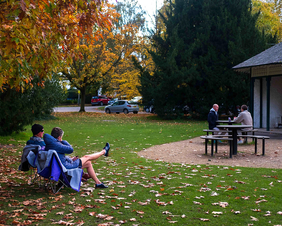A couple sit at a safe distance from other couples in Pittville Park, Cheltenham during UK's Coronavirus pandemic Lockdown.