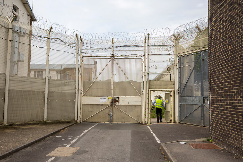 A gate into the secure section of HMP Coldingley. Surrey, United Kingdom. HMP Coldingley is a category C training prison, focussed on the resettlement of prisoners. All inmates must work a full working week, within the prison grounds. (Photo by Andy Aitchison)