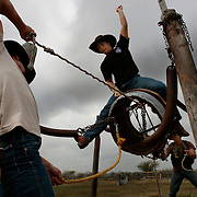 Gustavo Trevino, 17, practices his bull riding technique on a re-enforced wooden barrel as Jesse Villarreal, front, and Jerry Martinez, 17, behind, pull and twist him into the air during practice for the Weslaco Rodeo Club. The barrel, which is attached to four springs, teaches the young riders balance and technique before attempting to ride a bull. Members on the club practice in the evenings Monday through Friday and Saturday morning when they do not have a rodeo. The Weslaco Rodeo Club has about a dozen teenage members who on most weekends can be found throughout south Texas seeking glory by riding a bull for eight seconds.<br /> Nathan Lambrecht/The Monitor
