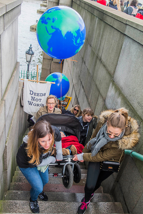Baloon Globes are issued as a symbol of international solidarity also demonstrated by teamwork in getting a buggy up some tricky stairs  - 'Walk in Her Shoes' a mother's day march in solidarity with women and girls around the world and in advance of International Womens Day this week - CARE International's Walk In Her Shoes event led by Helen Pankhurst, her 21-year old daughter Laura Pankhurst, music legend Annie Lennox, Bianca Jagger, comedian Bridget Christie, Secretary of State for International Development Justine Greening, London Mayoral candidates Sadiq Khan and Sophie Walker and a group of 'Olympic Suffragettes' in Edwardian clothing with banners. They were also joined by Sister Sledge.