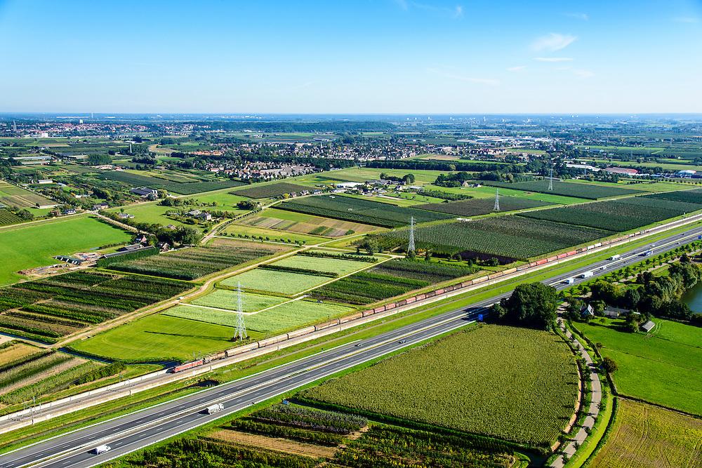 Nederland, Gelderland, Gemeente Neder-Betuwe, 30-09-2015; goederentrein passeert boomgaarden onderweg van Duitsland naar de Haven van Rotterdam op de Betuweroute. Omgeving Ochten, de autosnelweg A15 loopt parallell aan de spoorlijn.<br /> Freight train en route from Germany to the Port of Rotterdam on the Betuweroute.  A15 motorway runs parallell to the railroad.<br /> luchtfoto (toeslag op standard tarieven);<br /> aerial photo (additional fee required);<br /> copyright foto/photo Siebe Swart