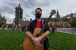 "© Licensed to London News Pictures. 28/10/2020. LONDON, UK.  A musician joins singers during ""Survival in the Square"", on day three of a week long series of creative activities taking place each day in Parliament Square.  The event is organised by #WeMakeEvents, an international movement to highlight that the live events sector urgently needs support from local governments to survive the Covid-19 crisis.  Photo credit: Stephen Chung/LNP"