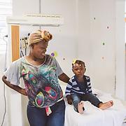 INDIVIDUAL(S) PHOTOGRAPHED: Julia Séjour (left) and Laura Louis (right). LOCATION: Sacré-Cœur Hospital, Milot Commune, Cap-Haïtien, Haïti. CAPTION: Julia Séjour with little Laura, her two-year-old daughter, in the maternity ward at the Sacré-Cœur Hospital in Milot.
