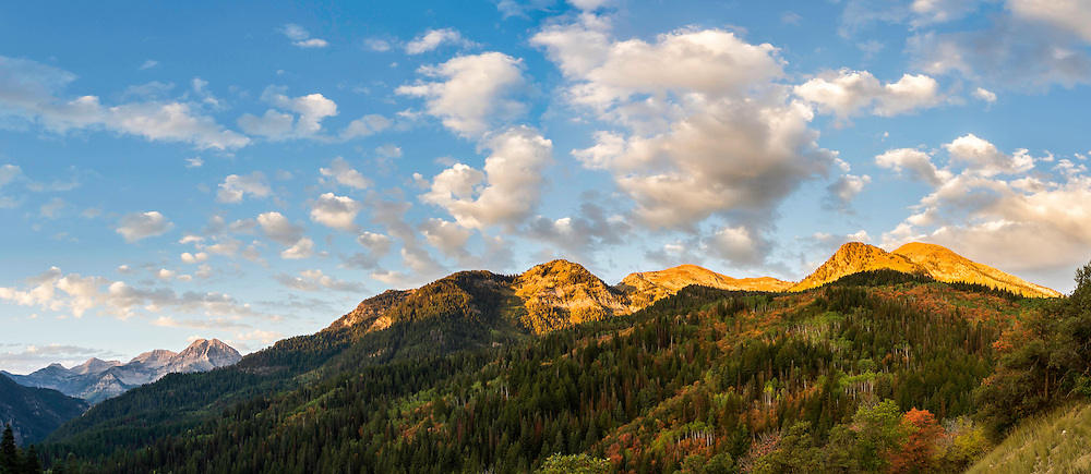 A Panoramic view of sunrise in American Fork Canyon during Fall colors in the Wasatch Mountains with Mount Timpanogos looming in the background.