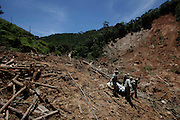 Firefighters, National force and residents recover the body of a landslide victim from a house where they found 8 family members in Nova Friburgo, Brazil, Thursday, Jan. 20, 2011. <br /> <br /> A series of flash floods and mudslides struck several cities in Rio de Janeiro State, destroying houses, roads and more. More than 900 people are reported to have been killed and over 300 remain missing in this, Brazil's worst-ever natural disaster.