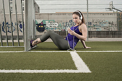 Young woman taking rest after exercising and listening to music on football ground, Bavaria, Germany