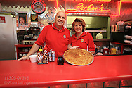 Charlie Parker's Diner owners, Mike and Cindy Murphy, pose at front counter with giant pancake which earns challengers a free meal if they can eat four in one sitting; Springfield, Illinois.