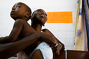 Kouadio Ahou Viviane waits with her 16-month-old boy Emmanuel Ngora Kwame at the NDA health center in Dimbokro, Cote d'Ivoire on Friday June 19, 2009. Emmanuel was suffering from fever, coughing, and a bloated abdomen.