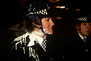 A woman police officer (WPC) stands with white paint plashed over her uniform during a public protest over the Poll Tax policies of Margaret Thatcher's government in 1990. It is dark and the trouble has been growing throughout the evening when the paint was thrown by unknown protesters. Angry crowds, demonstrating against Thatcher's local authority tax, eventually stormed the Whitehall area and then London's West End, setting fire to a construction site and cars, looting stores up Charing Cross Road and St Martin's Lane. The anti-poll tax rally in central London erupted into the worst riots seen in the city for a century. Forty-five police officers were among the 113 people injured as well as 20 police horses. 340 people were arrested.