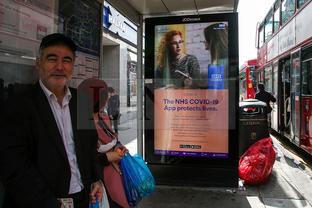 © Licensed to London News Pictures. 09/09/2021. London, UK. A woman looks at the government's 'The NHS COVID-19 App protects lives' latest advertising campaign poster displayed at a bus stop in north London as coronavirus infection cases continue to rise. As at 8 September, the UK recorded just under 39,000 new infections, an increase of 15.3% compared to the week before. Photo credit: Dinendra Haria/LNP
