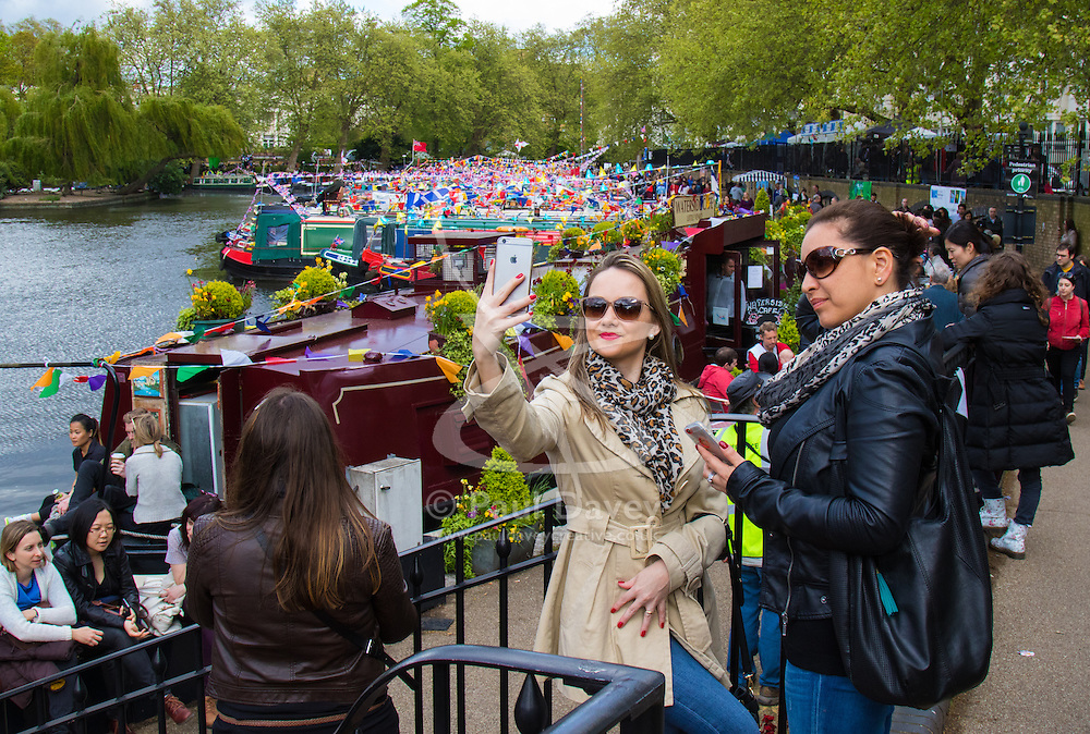 Little Venice, London, May 3rd 2015. After a dull, damp start to the day, hundreds of Londoners and narrowboat enthusiasts arrive at Paddington Basin at the juction of the Regents and the Grand Union Canals for the annual Inland Waterways Association's Canalway Cavalcade, celebrating the history and traditions of Britains vast network of canals and navigable rivers. PICTURED: A woman poses for a selfie against the backdrop of bunting-bedecked narrowboats.