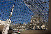Small-scaled tourists inside the giant pyramid of the Louvre art museum in Paris.