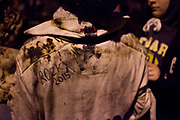 A shirt marked with tar and soon after tar barrel running. The annual running of the tar barrels in Ottery St Mary, Devon is a tradition thought to go back as far as 500 years. Every November the 5th, crowds of thousands flock to this small town in the south west of England to see men, women and children run with burning barrels on their shoulders. Only people who were born in Ottery are allowed to participate, and they are proud of the tradition and work hard to keep it alive, even in the face of health and safety regulations. It is not competitive but rather a supportive act where they pass the barrels between themselves, encouraging everyone in the team to have a go.