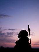Maasai tribesman at sunset looking over plains, Maasai Mara National Reserve, Kenya