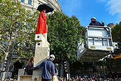 © Licensed to London News Pictures. 10/10/2019. LONDON, UK. Police in a cherry picker prepare to remove an activist secured to the top of a wooden structure in Trafalgar Square during day 4 of Extinction Rebellion's climate change protest in the capital.  Activists are calling on the Government to take immediate action against the negative impact of climate change.  Photo credit: Stephen Chung/LNP