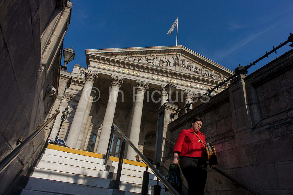 Neo-classical architecture of Cornhill Exchange, City of London. The lady is about to descend underground to Bank tube (subway) station beneath the converging columns of the famous Bank of England and Cornhill Exchange at Bank Triangle in the City Of London, the financial district, otherwise known as the Square Mile. The woman is on her way home in the afternoon, his commuting exodus to be shared by its daily working population of 311,000. This perspective suggests a bank and its architecture looking powerful and influential in the UK's economy. The pillars give a sense of establishment, a scene of classic stability and strength.