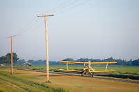 Crop duster taking off and landing on a small strip beside a road and power lines with poles in Arkansas