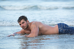 sexy muscular man in jeans and no shirt in the ocean
