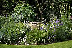 Empty urn in border with Geranium 'Johnson's Blue', Libertia grandiflora and sisyrinchium