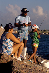 Stock photo of a family fishing from the shore on the coast