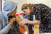 A TB Nurse Specialist checks for a BCG vaccination scar on a young man's arm.  This is part of a tuberculosis incident screening exercise conducted in a young people's hostel in central London, Uk, after a few residents were diagnosed with TB infection.