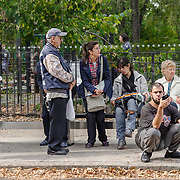 In a bus shelter at the start of the number 4 bus line. I love the diverse group of people, showing so many classic New York actions while waiting for the bus to arrive.