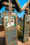 Tombstones in  The Merry Cemetery ( Cimitirul Vesel ),  Săpânţa, Maramares, Northern Transylvania, Romania.  The naive folk art style of the tombstones created by woodcarver  Stan Ioan Pătraş (1909 - 1977) who created in his lifetime over 700 colourfully painted wooden tombstones with small relief portrait carvings of the deceased or with scenes depicting them at work or play or surprisingly showing the violent accident that killed them. Each tombstone has an inscription about the person, sometimes a light hearted  limerick in Romanian. .<br /> <br /> Visit our ROMANIA HISTORIC PLACXES PHOTO COLLECTIONS for more photos to download or buy as wall art prints https://funkystock.photoshelter.com/gallery-collection/Pictures-Images-of-Romania-Photos-of-Romanian-Historic-Landmark-Sites/C00001TITiQwAdS8