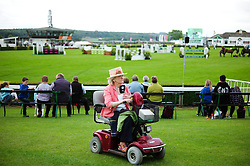 © Licensed to London News Pictures.14/07/15<br /> Harrogate, UK. <br /> <br /> A woman on a mobility scooter passes the main arena on the opening day of the Great Yorkshire Show.  <br /> <br /> England's premier agricultural show opened it's gates today for the start of three days of showcasing the best in British farming and the countryside.<br /> <br /> The event, which attracts over 130,000 visitors each year displays the cream of the country's livestock and offers numerous displays and events giving the chance for visitors to see many different countryside activities.<br /> <br /> Photo credit : Ian Forsyth/LNP