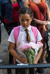 London, June 15th 2017. Local residents and well-wishers gather at a short vigil outside Notting Hill Methodist Church near the scene of the Grenfell Tower Fire Disaster in which so far seventeen people have been reported killed, with dozens injured, many still missing and scores of people rendered homeless. PICTURED: A girl lays flowers outside the church.