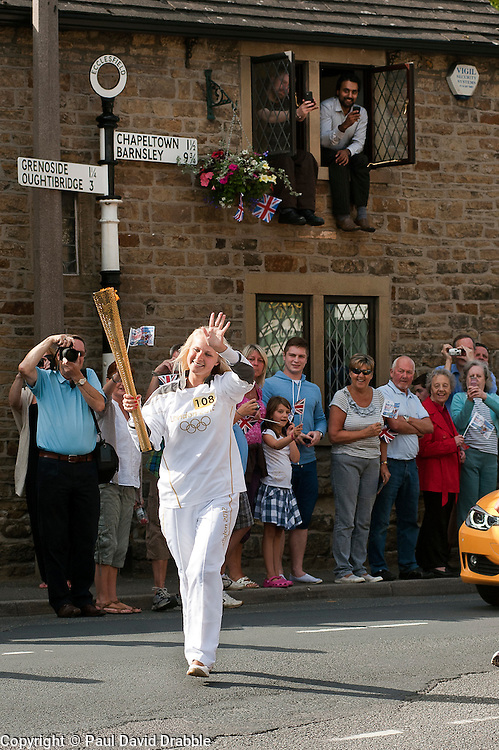 from the Chapeltown - Ecclesfield - Parson Cross section of the Journey.<br /> Locals take advantage of every possible vantage point as <br /> Torch bearer 108 Chloe Rutkowski aged 24 carries the flame up Church Street and onto Stocks Hill in her home Village of Ecclesfield<br /> 25 June 2012.<br /> Image © Paul David Drabble