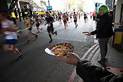 Jelly babies being handed out at the London Marathon on 28th April 2019 in London, England, United Kingdom. The London Marathon, presently known through sponsorship as the Virgin Money London Marathon, is a long-distance running event. The event was first run in 1981 and has been held in the spring of every year since. The race is mainly known for ebing a public race where ordinary people can challenge themsleves while raising great amounts of money for various charities.