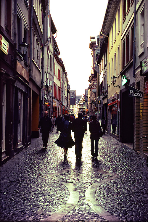 Three people walking through the narrow villiage of Mainz, Germany on cobblestone streets in the rain.