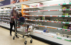 © Licensed to London News Pictures. 04/10/2021. London, UK. A shopper walks past nearly empty shelves of pre-cooked meat products in Sainsbury's, north London, amid fears of food shortages over Christmas. The Government and retailers warn that food and fuel shortages could continue until Christmas due to labour shortages following Brexit. According to Iceland, sales of frozen turkeys are up by more than 400 per cent compared to this time last year. Photo credit: Dinendra Haria/LNP