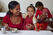 A mother and baby smile during meal time in the dining room at the Friends of Needy Children Nutritional Rehabilitation Centre, Kathmandu, Nepal.  The mother is feeding her child nutritious food as they are is an inpatient in the centre and receiving intensive treatment for malnutrition. The centre has recently been built to provide healthcare to malnourished children and education to mothers about nutrition and childcare.