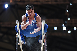 October 21, 2018 - Doha, Qatar - NIKOLAI KUKSENKOV from Russia puts chalk on his hands as he stands on the parallel bars during the first day of podium training before the competition held at the Aspire Dome in Doha, Qatar. (Credit Image: © Amy Sanderson/ZUMA Wire)
