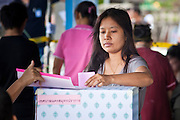 03 JULY 2011 - SAMUT PRAKAN, THAILAND:   A voter in Samut Prakan, Thailand, drops their ballot into the ballot box Sunday, July 3. More than 47,000,000 Thais were registered to vote in Sunday's election, which had turned into a referendum on the current government, led, by the Thai Democrats and the oppositionPheu Thai party. Pheu Thai is the latest political incarnation of ousted Thai Prime Minister Thaksin Shinawatra. PT is led by his youngest sister, Yingluck Shinawatra, who is the party's candidate for Prime Minister. Exit polling by three Thai polling firms showed Pheu Thai winning a landslide election.      PHOTO BY JACK KURTZ