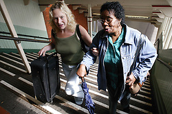 Two women walking up the stairs at a railway station,
