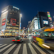 Evening traffic at a busy intersection in the Shubuya district of Tokyo.