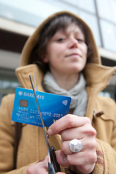 © licensed to London News Pictures. London, UK 27/04/2012. Ben Stewart cuts his Barclays debit cards outside Royal Festival Hall to protest against Barclays AGM today (27/04/12). Photo credit: Tolga Akmen/LNP