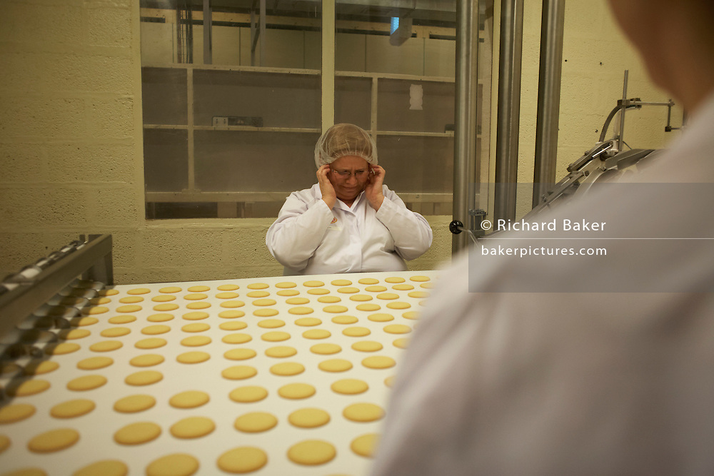 Quality control workers sort through sub-standard Moments biscuits at the Delacre biscuit production factory in Lambermont