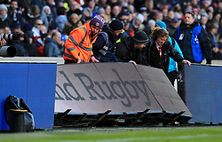 Staff pick up the advertising board after England and France players clash during the Guinness Six Nations match at Twickenham Stadium, London.