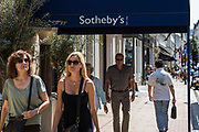 Pedestrians walk along the pavement underneath the street awning for Sotheby's, New Bond Street, London, United Kingdom.  Sotheby's is one of the word's largest brokers of fine and decorative art, jewelry, real estate and collectibles.  The multinational cooperation was originally British and established in 1744, but now headquartered in New York City.