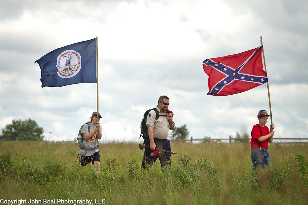 From left, Lindsay Smith, 10, father, Greg, and brother, Rocco, 12, of Smithsburg, Maryland, walk to join thousands of others to participate in the Pickett's Charge Commemorative March, during the Sesquicentennial Anniversary of the Battle of Gettysburg, Pennsylvania on Wednesday, July 3, 2013.  Visitors were given the opportunity to follow in the footsteps of Confederate soldiers by walking with living historians and park rangers along the path of the famously ill-fated Pickett's Charge, which brought to a close The Battle of Gettysburg when the Union Army repelled their advance. The Battle of Gettysburg lasted from July 1-3, 1863 resulting in over 50,000 soldiers killed, wounded or missing.  John Boal Photography